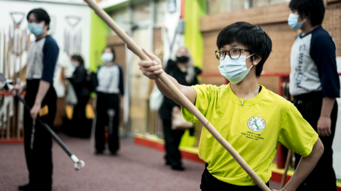 Young Martial artist with yellow t-shirt and staff