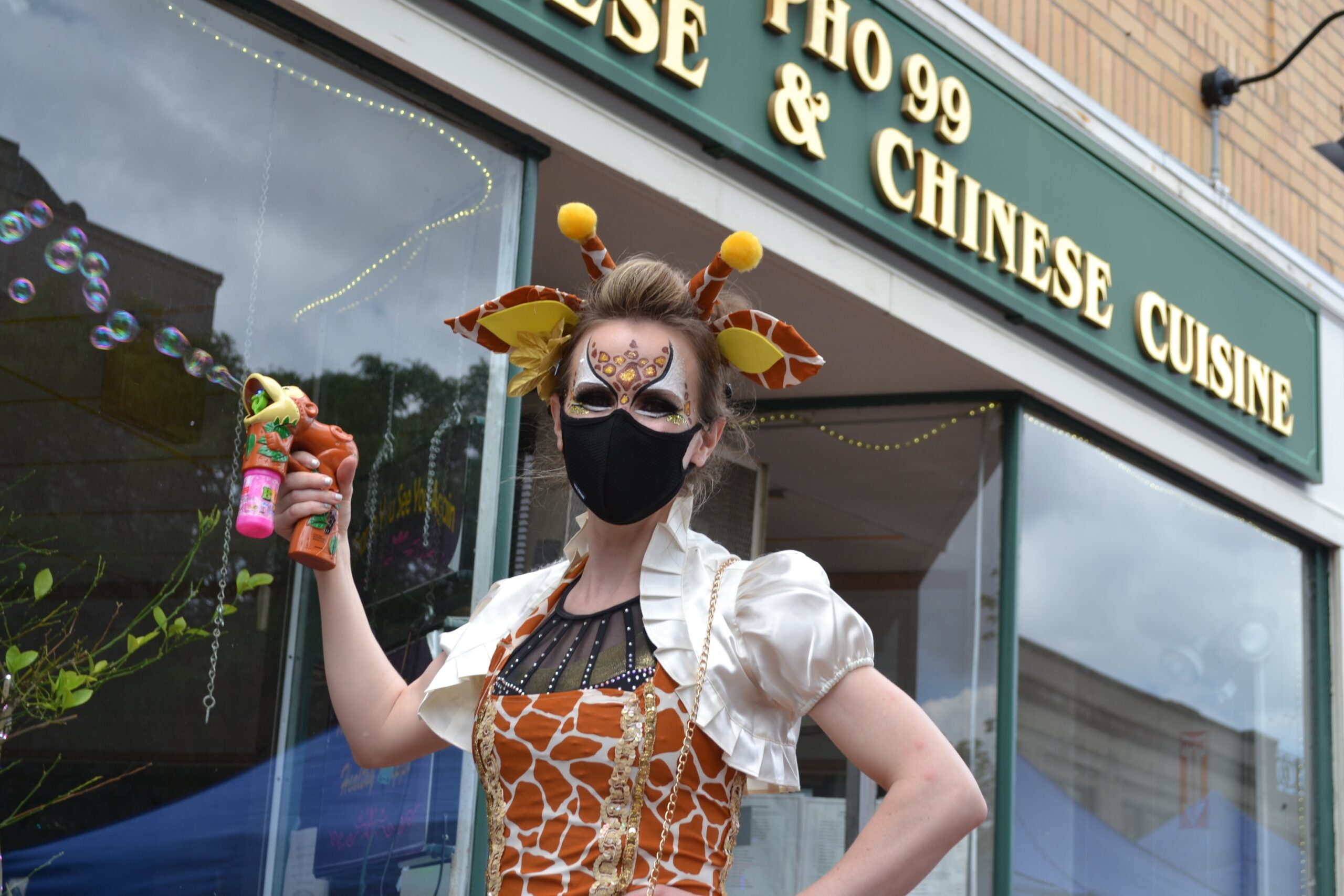 Performer with painted face in front of Chinese restaurant